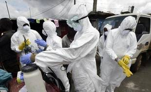 Des membres de la Croix-Rouge se préparent à récupérer le corps d'une victime du virus Ebola, le 4 octobre 2014 dans le quartier de West Point, à Monrovia, au Liberia