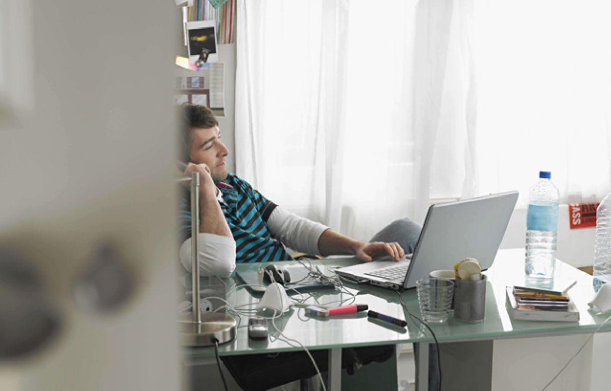 Un homme qui travaille chez lui avec un téléphone et un ordinateur. –  Gary Burchill / Mood Bo/REX/SIP