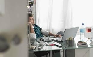 Un homme qui travaille chez lui avec un téléphone et un ordinateur.