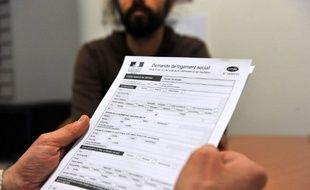 Une personne tient un document de demande de logement social dans un bureau d'aide sociale, le 30 Janvier 2012 à Tours.