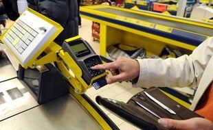 Illustration d'un paiement par carte bancaire dans un supermarché.