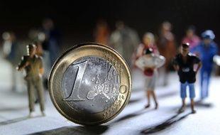 Une pièce d'un euro devant des figurines.