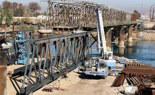 Des fermiers irakiens réparent un pont détruit lors de la bataille de Mossoul, le 9 janvier 2018.