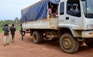 Des travailleurs de la plantation d'hévéas, qui appartient au géant singapourien Olam, montent dans un camion à la fin de leur journée à Batouri, dans le nord du Gabon, le 30 avril 2015