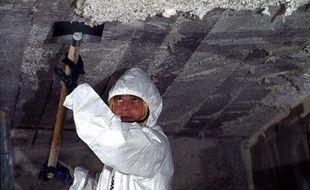 Un employé retire de l'amiante du plafond d'une école primaire à Nantes.