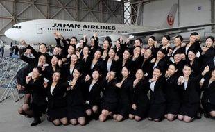 Les nouvelles hôtesses recrutées par Japan Airlines posent devant un Boeing 777 à Tokyo le 1er avril 2015, au cours de la cérémonie qui marque le début de carrière de 1.067 nouvelles recrues pour les 30 entreprises du groupe JAL