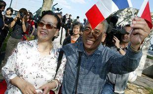 Les premiers touristes chinois «officiels» en provenance de Pékin  brandissent des drapeaux francais et chinois, le 01 septembre 2004 à  leur arrivée à l'aéroport de Roissy.