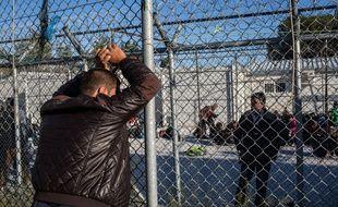 Camp de Moria sur l'île grecque de Lesbos. Un migrant discute avec un autre, qui se trouve a l'intérieur du hotspot, le 27 octobre 2015.