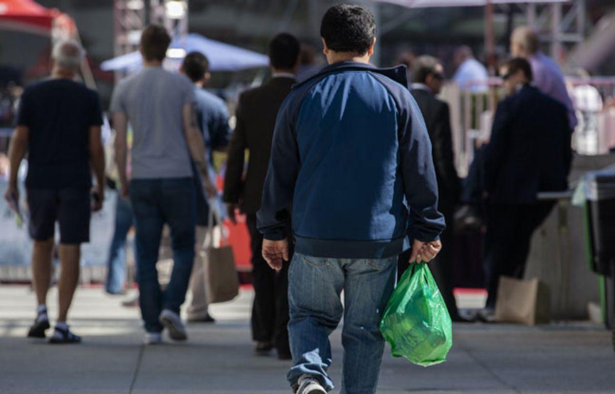 Illustration d'un homme tenant un sac plastique.  – Kimberly White / GETTY IMAGES NORTH AMERICA / AFP
