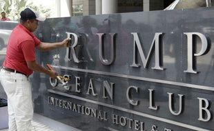 Un ouvrier ôte une à une les lettres formant «Trump» à l'entrée du Trump Hotel de Panama City, le 5 mars 2018.