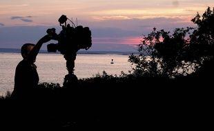 Une équipe de tournage pose sa caméra près de la rive de l'Ile Bailey où une Américaine de 63 ans a été attaquée et tuée par un requin blanc ce lundi 27 juillet.