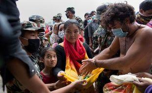 Des Népalais reçoivent de la nourriture auprès d'une ONG à Katmandou, le 30 avril.