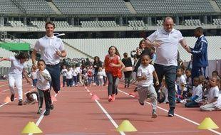 Patrick Baumann (à droite) et Tony estanguet font la course avec des enfants, lors de la visite du CIO au Stade de France, le 15 mai 2017.