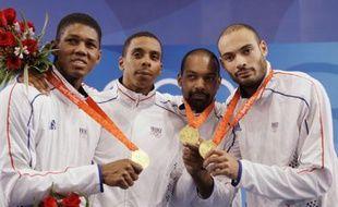 Jérôme Jeannet,  Fabrice Jeannet et Ulrich Robeiri sur la plus haute marche de l'épée par équipe avec le quatrième homme: le remplaçant Jean-Michel Lucenay, privé de médaille, le vendredi 15 août à Pékin.