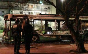 Des policiers se tiennent devant le bus de voyageurs partiellement incendié dans la cité du Grand Ensemble, à Tremblay-en-France, le 31 mars 2010.