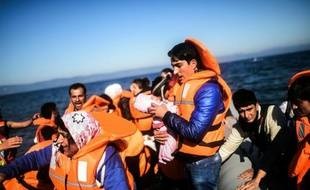 Une homme porte un nouveau né à son arrivée avec d'autres réfugiés sur l'île de Lesbos en Grèce, après une traversée en canot pneumatique de la mer Egée depuis les côtes turques, le 12 novembre 2015