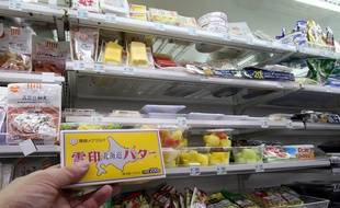 Un client tient une plaquette de beurre dans un magasin de Tokyo, le 10 novembre 2014.