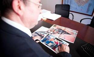 L'adjoint au maire de Nanterre, André Cassou, regarde des photos de la tuerie de conseil municipal du 27 mars 2002 (photo prise lundi 26 mars 2012)