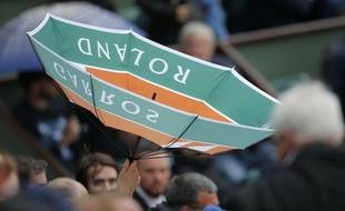 A spectator's umbrella is upside down as rain delays the play between France's Kristina Mladenovic and Timea Bacsinszky of Switzerland during their quarterfinal match of the French Open tennis tournament at the Roland Garros stadium, Tuesday, June 6, 2017 in Paris.