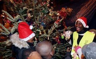 Mal-logés et sympathisants de l'association Droit au Logement (Dal) ont organisé mercredi soir un Noël de fortune pour les enfants, au pied du campement de tentes et de bâches rue de la Banque dans le centre de Paris.