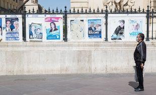 Un homme devant les affiches des élections municipales à Marseille.