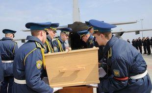 Des soldats ukrainiens soulèvent le cercueil contenant les restes de l'une des victimes du crash du vol MH17 de la Malaysia Airlines, le 28 mars 2015.
