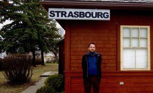 Jean-Yves Bart devant l'ancienne gare de Strasbourg dans la région canadienne du Saskatchewan.