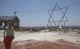 Un colon juif devant l'Etoile de David et un nouveau bâtiment en construction dans la colonie illégale de Ramat Gilad, en Cisjordanie.