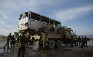 Des soldats afghans se tiennent près d'un bus contre lequel s'est jeté un kamikaze, tuant trois soldats, le 8 février 2016 à Dehdadi, dans l'agglomération de Mazar, en Afghanistan
