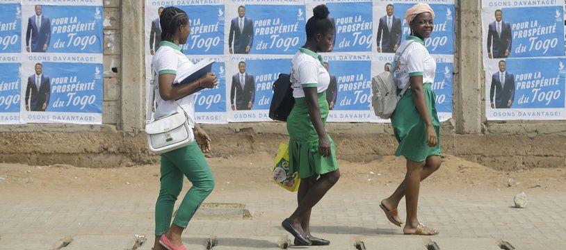 Des lycéennes devant des affiches électorales du président sortant, Faure Gnassingbe, le 21 février 2020 à Lomé.