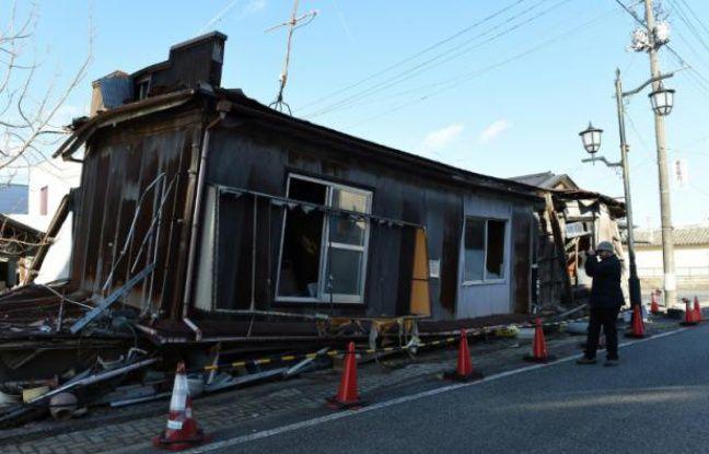 """Un """"touriste"""" photographie une des maisons abandonnées de Namie, dans la région de Fukushima, le 11 février 2016, 5 ans après l'accident nucléaire"""