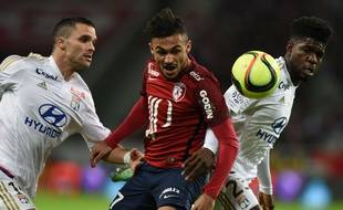 Lille's French midfielder Sofiane Boufal (C) vies with Lyon's French Cameroonian defender Samuel Umtiti (R) and Lyon's French defender Jeremy Morel during the French L1 football match between Lille (LOSC) and Lyon (OL) on February 21, 2016, at Lille Pierre Mauroy stadium in Villeneuve-d'Ascq, northern France. AFP PHOTO / DENIS CHARLET