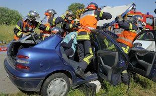 Des pompiers désincarcèrent une voiture au cours d'un exercice simulant un carambolage.
