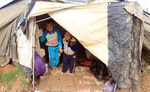 Des enfants debout dans leur tente dans un camp de réfugiés à Erbil, capitale du Kurdistan. Credit : Yaser Jawad/CHINE NOUVELLE/SIPA.