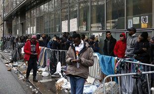 Des migrants font la queue pour déposer une demande d'asile, à Paris, jeudi 21 décembre.