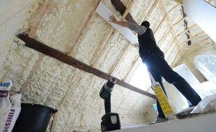 Travaux d'isolation du toit d'une maison.