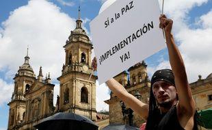 Un homme brandit une pancarte demandant la paix avec les Frac devant le parlement colombien à Bogota en Colombie.