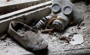 Un masque à gaz pour enfant et un chausson sont abandonnés dans un jardin de la ville fantôme de Prypiat près de la centrale nucléaire de Tchernobyl, Ukraine, le 4 avril 2011.