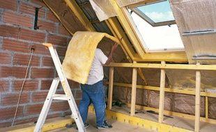 Un artisan dépose un rouleau de laine de verre entre les éléments structurels de la toiture pour l'isoler thermiquement les combles.
