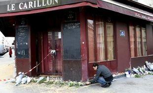 """Un homme rend hommage aux victimes des attaques du restaurant """"Le Carillon"""" , le 14 novembre 2015 à Paris"""