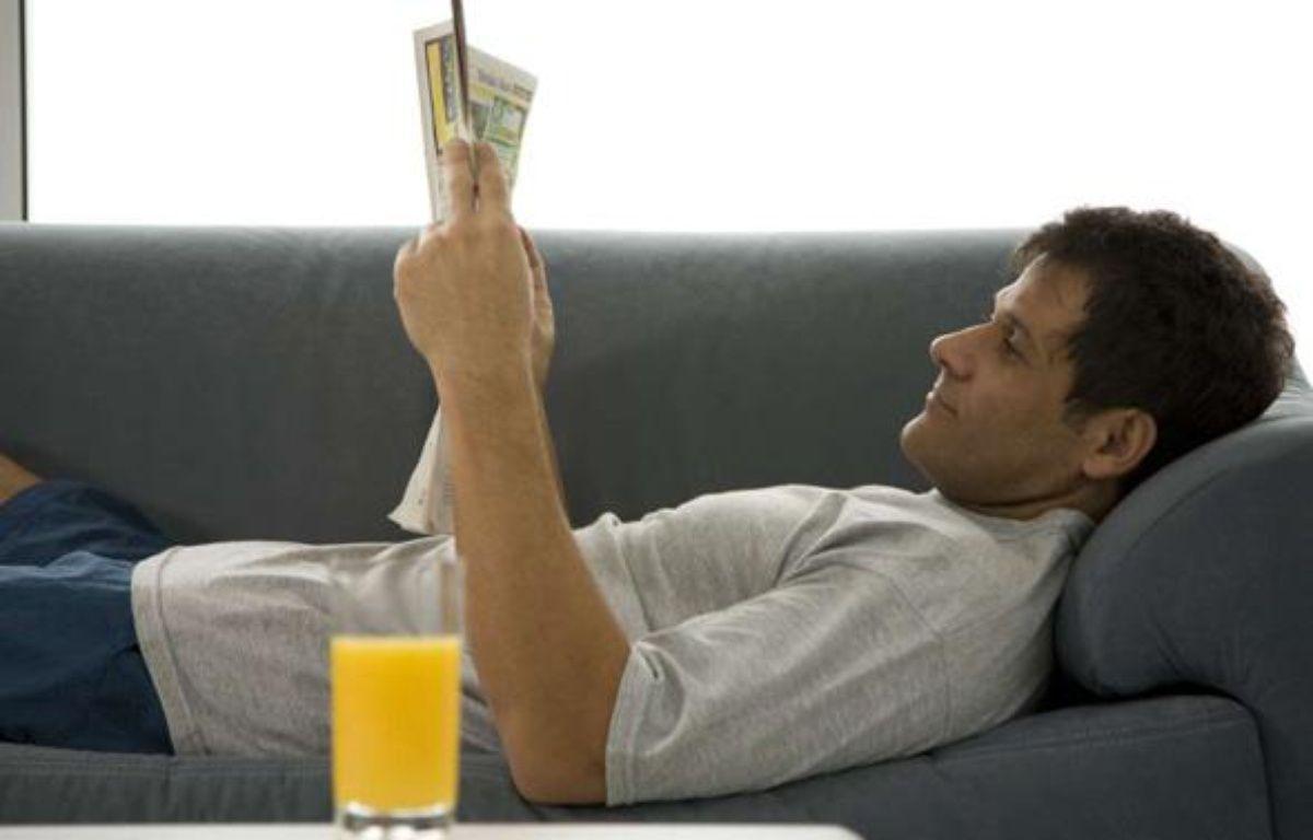 Un homme lit le journal sur son canapé. – PureStock/SIPA