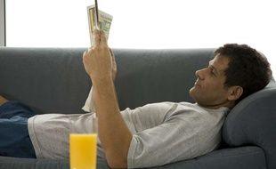 Un homme lit le journal sur son canapé.