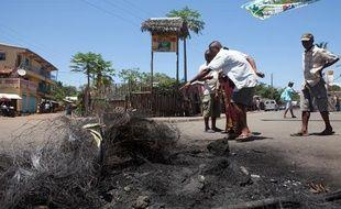 Des passants devant le lieu où a lieu le lynchage de trois personnes à Madagascar le samedi 5 octobre 2013.