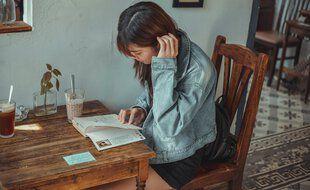 Une adolescente en pleine lecture chez elle.