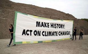 Des militants d'Oxfam déploient une banderole à Lima, au Pérou,  le 29 novembre 2014.
