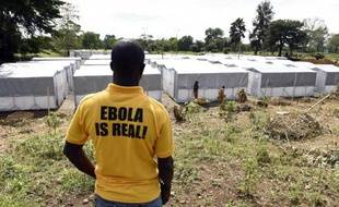 """Un homme portant un T-shirt """"Ebola est réel"""" regarde le nouveau centre de traitement des malades atteints du virus Ebola à Monrovia, le 28 septembre 2014"""