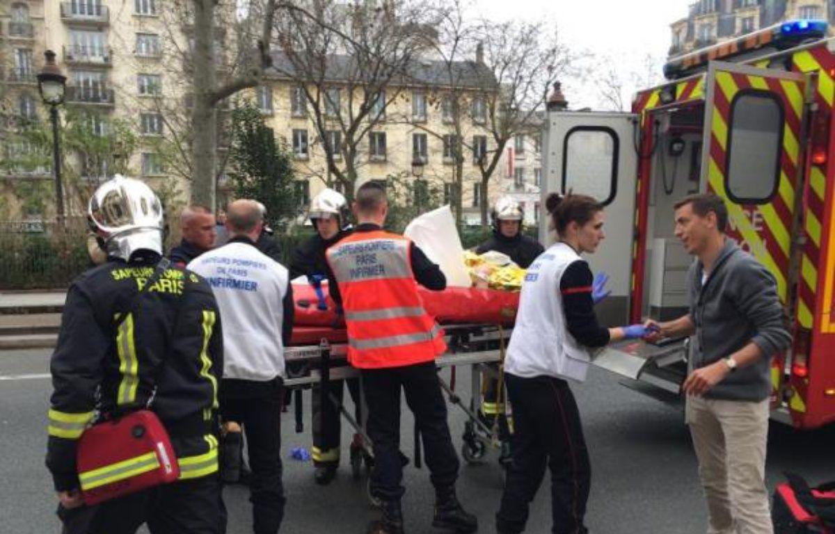 Des pompiers prennent en charge une personne blessée lors de l'attentat contre Charlie Hebdo le 7 janvier 2015 à Paris – Philippe Dupeyrat AFP