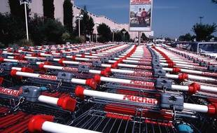 Rangées de caddies dans un supermarché Auchan.