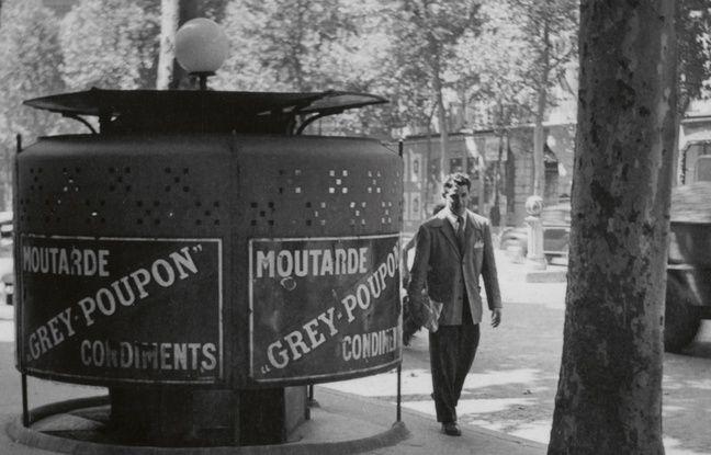 Paris 1948, un homme passe à côté d'une vespasienne