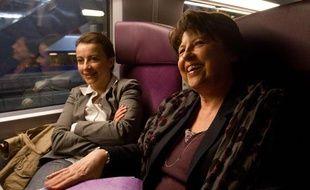 Cécile Duflot (à gauche) d'EELV et Martine Aubry (à droite) du PSdans un train Paris-Le Mans, en campagne pour les élections cantonales, le 23 mars 2011.